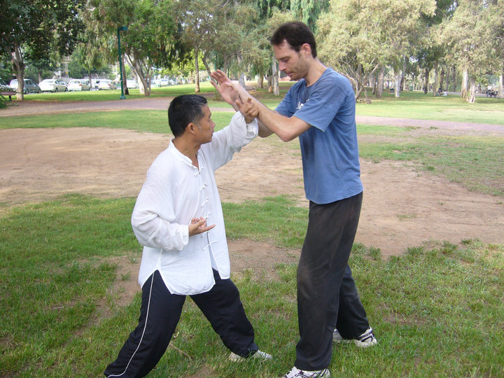 Master Zhou, demonstrating application with his Israeli student, Etai. During this particular moment, Zhou was showing how proper alignment and structure, as developed through Zhan Zhuang training, can make it easy for a small person to resist a much larger individual. Zhou is roughly 5'6 in height, and Etai is 6'4. HaYarkon Park, Tel-Aviv, Israel, August 2010.