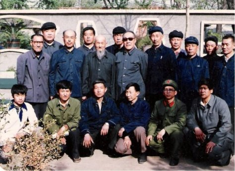 Members of Zhou's gongfu family – practitioners of Baji Quan and Jingang Bashi, together with members of the Communist Party. Circa 1980s. Zhou is sitting in the front row, on the far left, wearing a white shirt. Behind Zhou stands his grand-teacher, Tian Jinzhong, wearing glasses. To Tian's left stands another grand-teacher of Zhou's – Zhao Fujiang (bald man with dark-blue shirt), who was master Tian's younger gongfu brother in their Baji lineage.